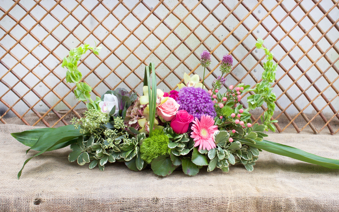 HEPATICA table centerpiece (allium, bells of ireland, cymbidium orchid, roses, gerbera daisy, lily grass) – photo: QUARTER design studio
